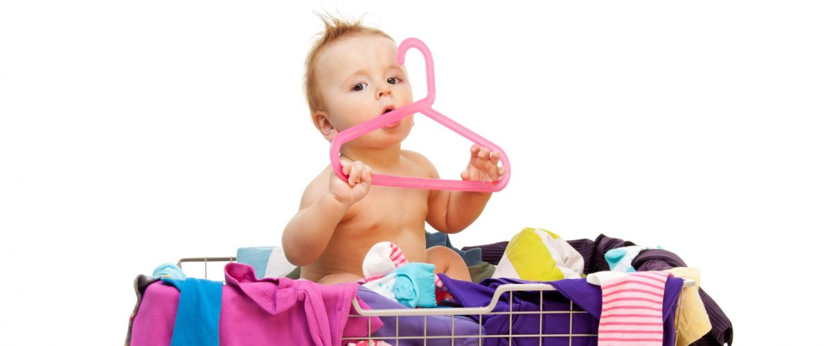 Baby in basket with clothes with hanger, isolated on white